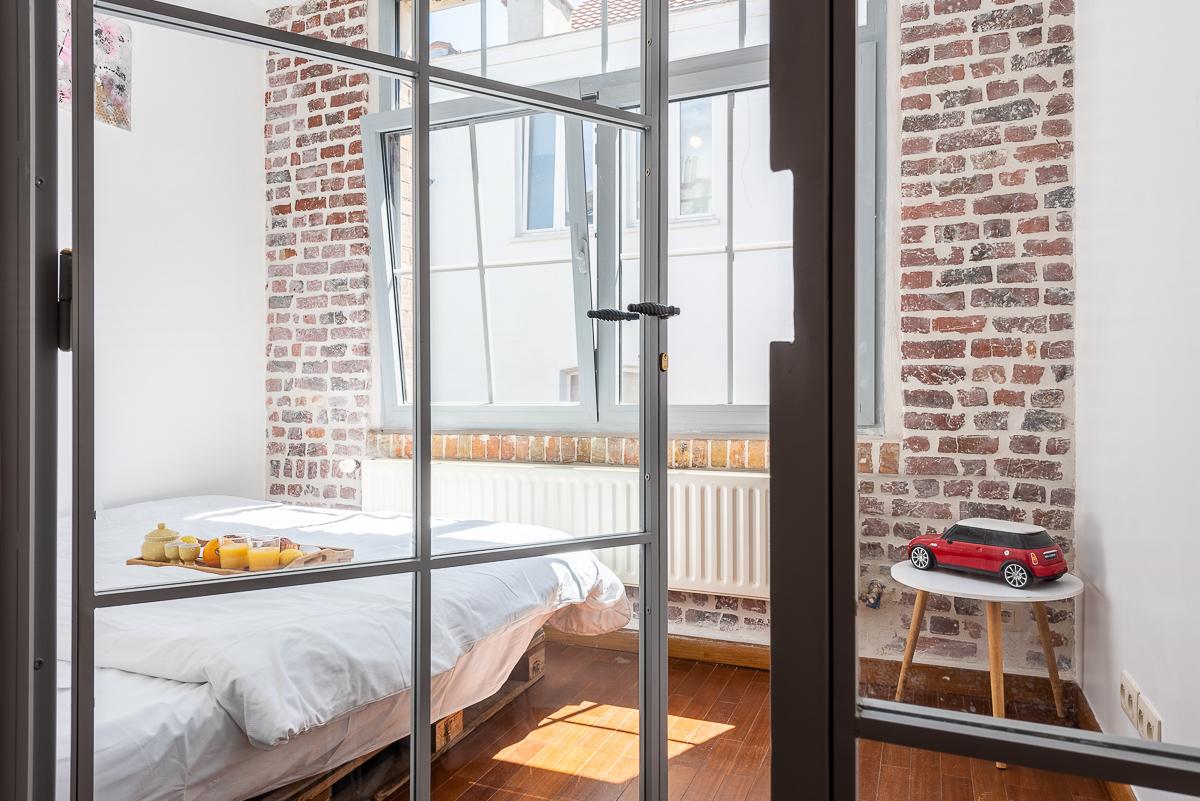 Vue intérieure d'une chambre à travers une porte vitrée